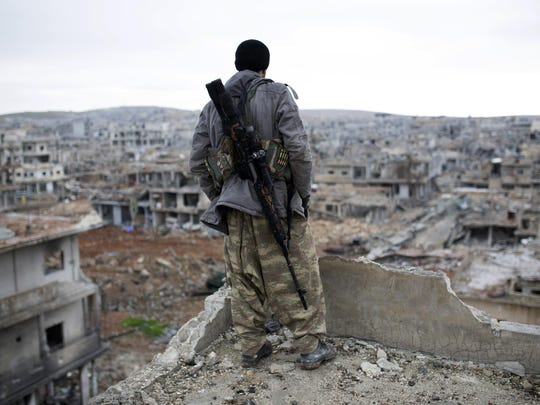 A Syrian Kurdish sniper looks at the rubble in the Syrian city of Kobani. In 2015, the U.S. went to the aid of Syrian Kurds who fought to the death against ISIS for five months over the city. Now, Kobani is besieged again, this time by Turkey.