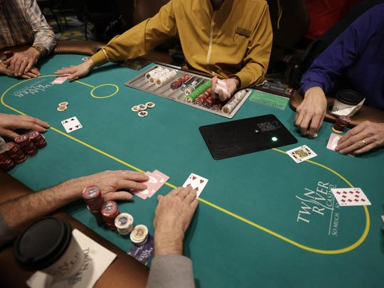 A casino employee deals a game of poker to patrons at Twin River Casino in Lincoln, R.I.