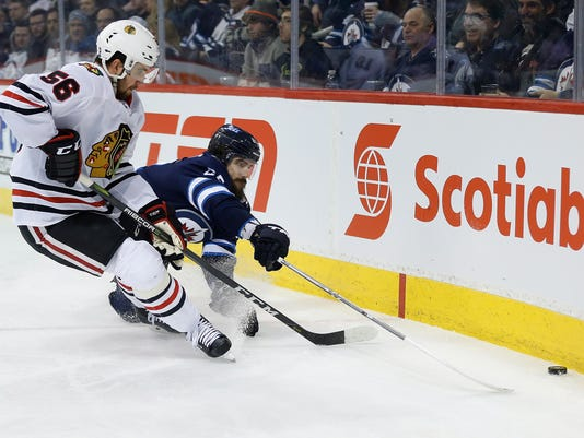 Winnipeg Jets center Mathieu Perreault (85) and Chicago Blackhawks defenseman Erik Gustafsson (56) go for the loose puck during the second period of an NHL hockey game Thursday, March 15, 2018, in Winnipeg, Manitoba. (John Woods/The Canadian Press via AP)