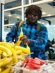 A Pocomoke student grabs fruit as part of breakfast