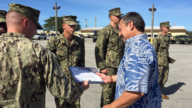 At Naval Base Guam on Wednesday, Lt. Cmdr. Travis Brinkman hands a certificate of appreciation to Gov. Eddie Calvo as he prepares to present it to Alex Zebro of the Naval Mobile Construction Battalion. Zebro was one of nine Seabees recognized for helping the Guam Vet Center on Veterans Day this past November.