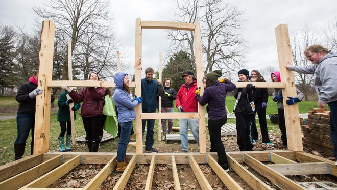 SUNY Geneseo students work on frame of replica cabin.