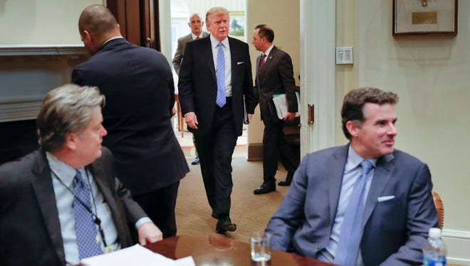"President Donald Trump walks in from the Oval Office of the White House in Washington in Washington, Monday, Jan. 23, 2017, before hosting breakfast with business leaders in the Roosevelt Room. Sitting at the table is White House Senior Adviser Steve Bannon, left, and Kevin Plank, founder, CEO and Chairman of Under Armour. Plank drew criticism this week when he praised Trump as an ""asset"" for the country."