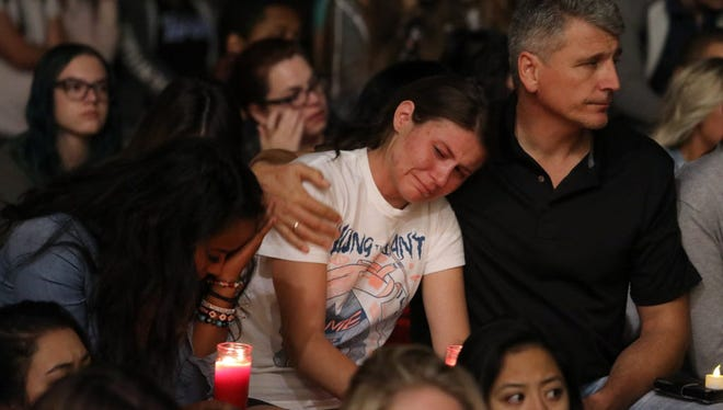 Mourners react during a candlelight vigil at the University of Nevada Las Vegas (UNLV) for victims of a mass shooting in Las Vegas, Nev.