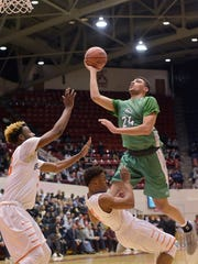 Novi Wildcat Tariq Woody (24) heads for the basket. Belleville's Connor Bush (33) and Cameron Smiley (2) can't stop him.