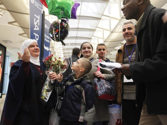Reem Kabbani, left, spoke with Kentucky Refugee Ministries case worker Napoleon Akayezu, right, while her son Mohammed Hadi Haj Omar gazed at balloons that were given to home. the family of Syrian refugees arrived at Louisville International Airport as President Donal Trump was being sworn into office. Jan. 20, 2017