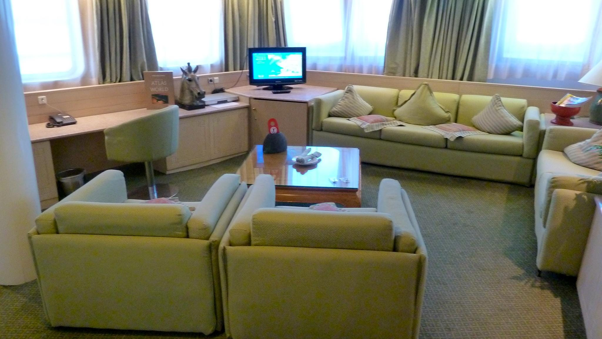 The living room of the Mandarin Suite has two settees and two comfortable chairs, a large flat-screen television, writing desk and panoramic picture windows.