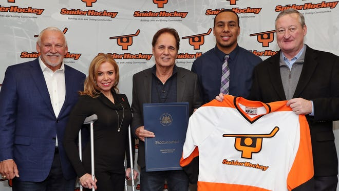 Scott Tharp, center, is the president of the Ed Snider Youth Hockey Foundation. He is carrying on the legacy of the Flyers' late owner. He stands Saturday with Bernie Parent, Sheila Hess, Jonathan Quinones and Philadelphia mayor Jim Kenney.