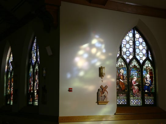 A stained glass window depicting Jesus being taught