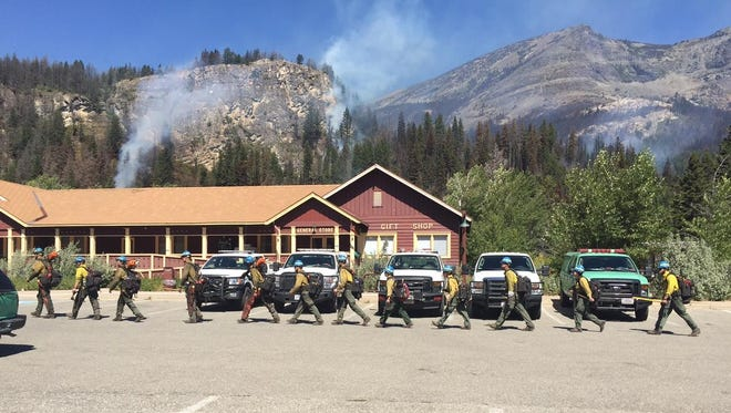 Firefighters march past the general store at Rising Sun on their way to work on the Reynolds Creek Fire in Glacier National Park.
