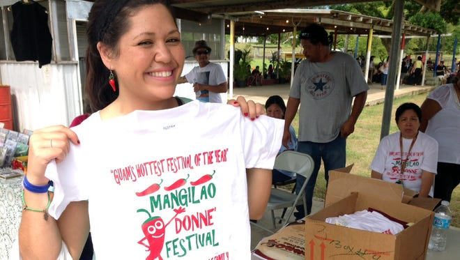 Tamuning resident Cristina Nellis, 26, holds up a T-shirt at the 5th Annual Mangilao Donne' Festival on Sept. 13.