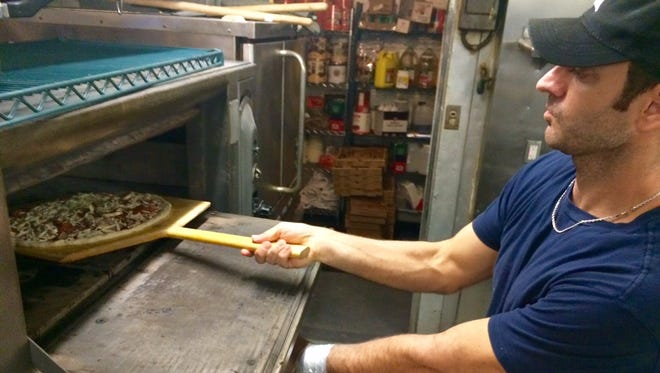 Owner Mike Amato places a pizza in the oven at Overtime Pizzeria and Sports Bar in Cape Coral.
