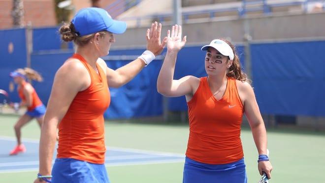 Florida teammates Kourtney Keegan, left, and Brooke Austin high-five after winning the NCAA doubles title.