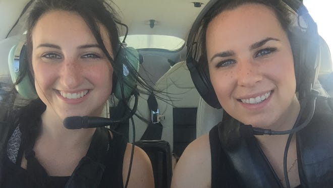 Co-pilot Mary McCarty, left, and pilot Molly Van Scoy pose inside the Cirrus SR20 plane they flew in the Air Race Classic last week.