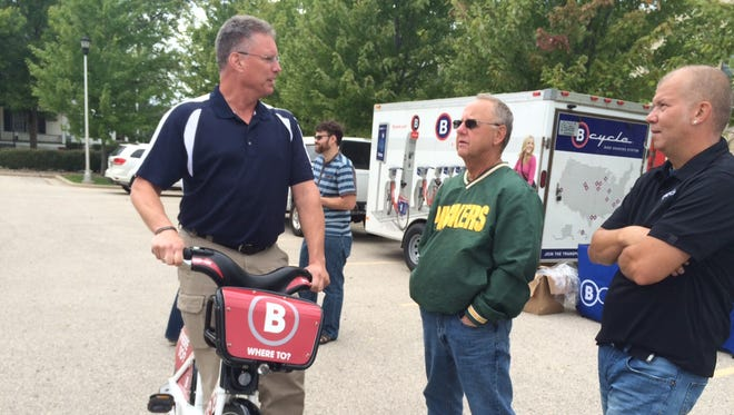 Rick Moulton tests BCycle's public rental bicycle, as he chats with Pete Doll and Jake Higdon, a demonstration coordinator with the company. BCycle demonstrated its bike share program in Fond du Lac's Hamilton Park Monday.