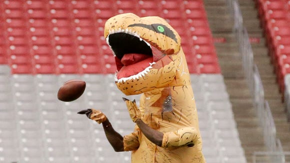 Arizona Cardinals cornerback Patrick Peterson catches a pass while dressed as a dinosaur prior to an NFL football game against the New York Jets, Monday, Oct. 17, 2016 in Glendale, Ariz.
