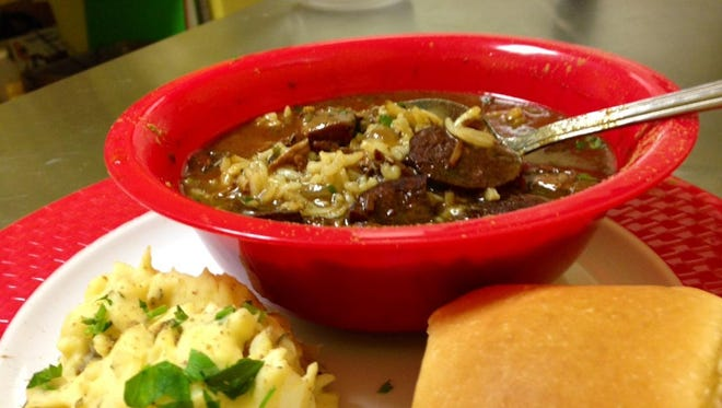 A bowl of gumbo with a dark rich broth and andouille sausage and rice peeking out, served with a side of creole potato salad at A Cajun Bowl.