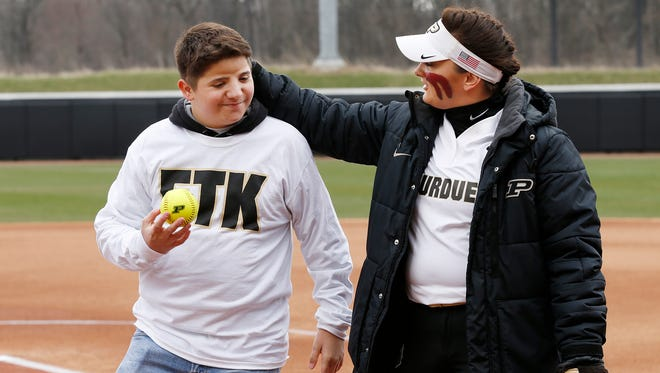 Purdue junior pitcher Kaitlynn Moody gives her younger brother Ayden, 13, a pat on the back after he threw the honorary fist pitch to her before the Boilermakers' Strike Out Cancer game against Northwestern Friday, April 6, 2018, at Bittinger Stadium. Ayden has undergone 13 operations, including four skull operations and spinal cord surgery. The event was in conjunction with Riley Hospital for Children. Ayden was named a Riley Champion in 2010.