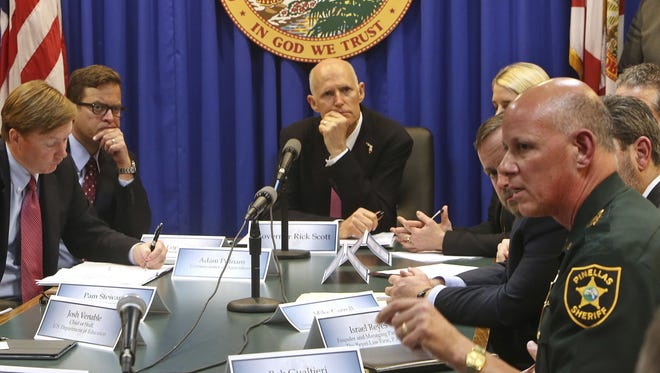 Pinellas Sheriff Bob Gualtieri, right, responds to a question from Florida Gov. Rick Scott, back, on gun violence during a meeting at Florida's Capitol, Tallahassee. At left is State Agriculture Commissioner Adam Putnam and Lt. Gov. Carlos Lopez-Cantera.