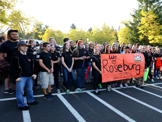 Roseburg marching band stands with a banner signed
