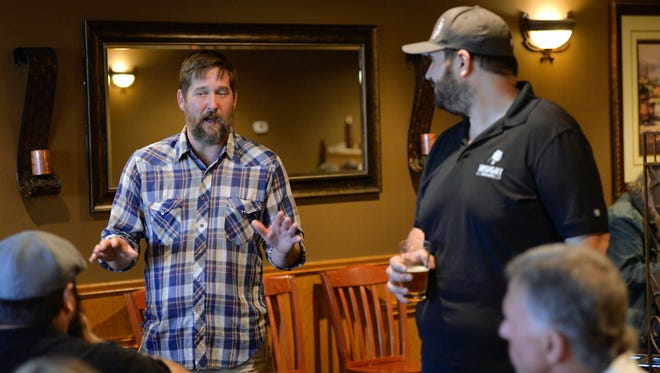 Insight Brewing's Head Brewer Ryan Mihm, left, and Sales Manager David Munk talk about the concept for Thursday's beer dinner at the Ace Bar and Grill in St. Cloud.