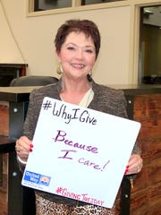 """Terri Axell holds a sign explaining why she gives to United Way of the Mid-Willamette Valley. """"Because I care!"""" the sign reads. United Way took photos of their donors explaining their giving motivations to promote #GivingTuesday."""