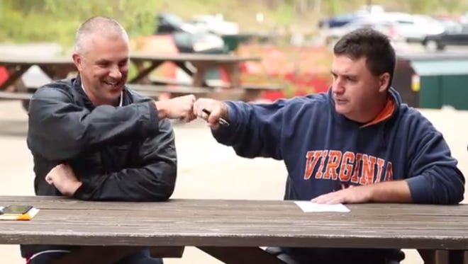 Sports producer Dean Russin, left, shares a fist-bump with sports writer Rob Centorani during a September video shoot.