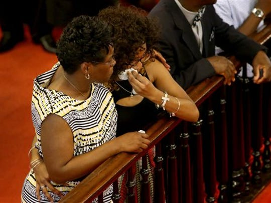 People kneel during a prayer in a worship service at