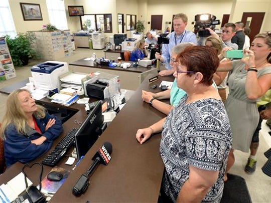 Karen Roberts, center, and her partner April Miller speak with Rowan County Clerk Kim Russell in an attempt to obtain a marriage license at the Rowan County courthouse in Morehead, Ky., Thursday, Aug. 13, 2015. Miller and Roberts, two of the original plaintiffs in the federal suit against Rowan County, Ky., and Rowan County Clerk Kim Davis were at the courthouse to obtain a marriage license. The clerk's office rejected the couples' bid for licenses just hours after U.S. District Judge David L. Bunning ordered Davis to comply with the Supreme Court's ruling.