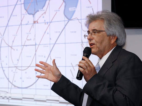 FILE - In this Sept. 12, 2016 photo, Matt Skinner, public information officer at the Oklahoma Corporation Commission, speaks during a news conference on recent earthquake activity, in Oklahoma City. At rear is a map of the area of activity.  An AP analysis shows earthquakes in Oklahoma have been cut in about half since new regulations were put in place to limit wastewater injections into energy wells.