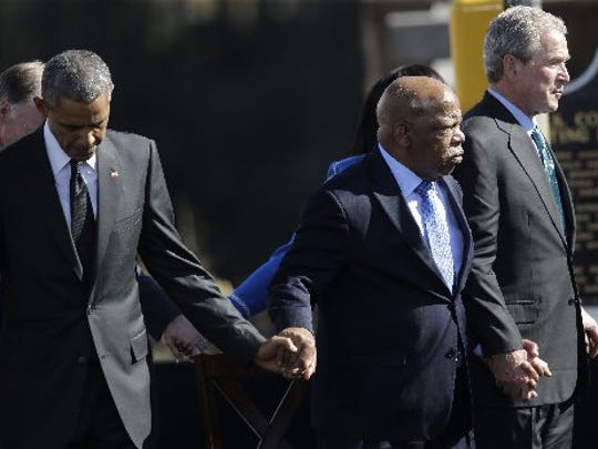 "President Barack Obama, left, U.S. Rep. John Lewis, D-Ga., and Former President George W. Bush hold hands for a prayer after Obama spoke near the Edmund Pettus Bridge, Saturday, March 7, 2015, in Selma, Ala. This weekend marks the 50th anniversary of ""Bloody Sunday, ' a civil rights march in which protestors were beaten, trampled and tear-gassed by police at the Edmund Pettus Bridge, in Selma."