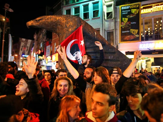Supporters of the 'no' vote, one, holding a banner of modern Turkey's founder Mustafa Kemal Ataturk, centre, chant slogans during a protest against the referendum outcome, in Istanbul, Tuesday, April 18, 2017. Hundreds of people are queuing in front of Turkey's election board in capital Ankara to submit petitions requesting that the electoral authority reverse a controversial decision during Sunday's referendum to accept ballots without official stamps, as required by Turkish law.