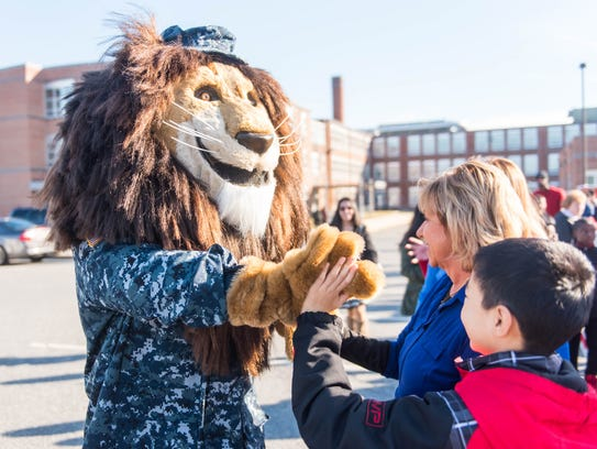 Sgt. Roary the Lion high fives a student at Veteran's