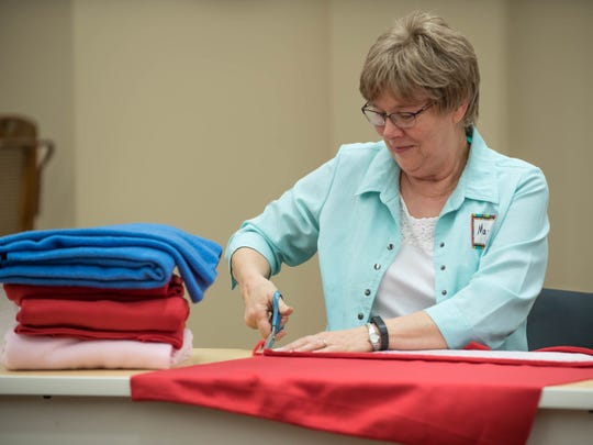 George Award winner Mary Embury cuts material for a baby sleeper.