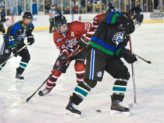 St. Cloud Icebreakers's Sophia O'Neal, 29,  and Sartell/Sauk Rapids' Brooke Walters battle for the puck during the first period Friday, Jan. 19, during Hockey Day Minnesota at Lake George.