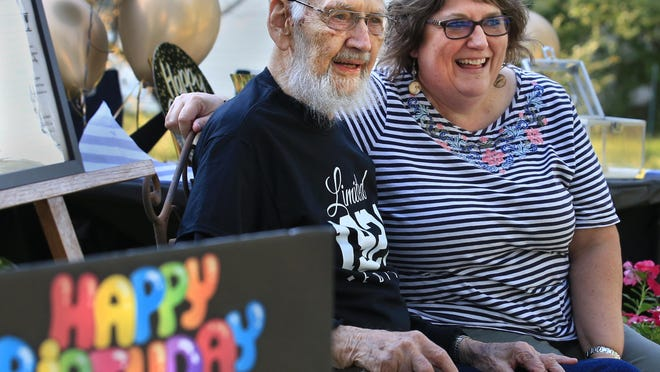 Daniel Penner looks at all the vehicles pulling through his driveway, with his daughter-in-law Susan Penner, as he celebrates his 100th birthday Thursday, Aug. 20.