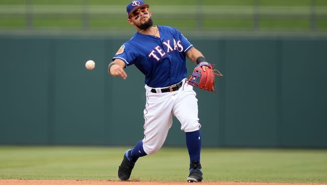 Texas Rangers second baseman Rougned Odor (12) throws out a runner at first base during the fourth inning against the Chicago Cubs at Surprise Stadium.