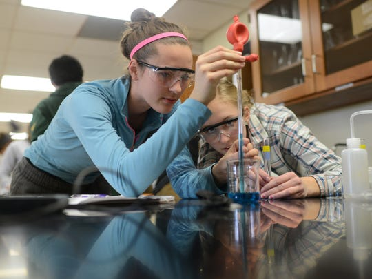 De Pere high school students Lindsey Mirkes and Karly Skaletski use a pipette to draw a stock solution for an experiment to determine how much food coloring is used in commercially available beverages.