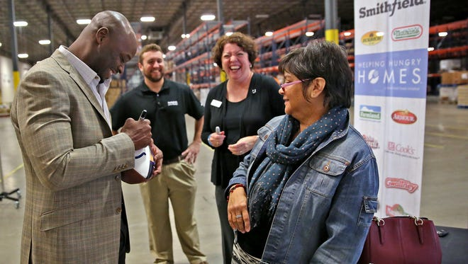 "Former Indianapolis Colts receiver Reggie Wayne, from left, laughs and signs autographs with Gleaners' Todd Norman and Sarah Estell, and Smithfield Foods' Chris Holcomb at Gleaners Food Bank, Friday, October 14, 2016, after the announcement that Smithfield is donating more than 50,000 pounds of protein to Gleaners as part of the company's nationwide ""Helping Hungry Homes"" tour."
