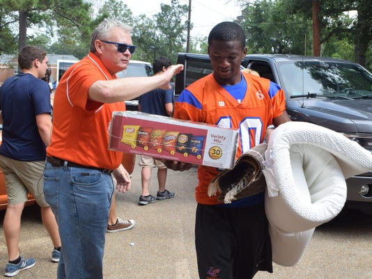 ANI LC move-in day Louisiana College president Dr. Rick Brewer (left) pats LC Wildcats football player Farron Jones (right) on the back as he and his teammates help students move items into Cottingham Hall on the Louisiana College campus. -Melinda Martinez