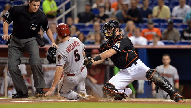 Aug 16, 2014: Marlins catcher Jeff Mathis (6) tags out Arizona Diamondbacks center fielder Ender Inciarte (5) at home plate during the first inning  at Marlins Ballpark.