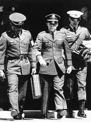 Flanked by two military policemen carrying his personal belongings, Lt. William Calley, Jr., of Miami, Fla., leaves court at Fort Benning, Ga., April 1, 1971, after he was sentenced to life imprisonment. Calley was found guilty of murder of Vietnamese civilians at My Lai three years ago by a six officer court martial panel.