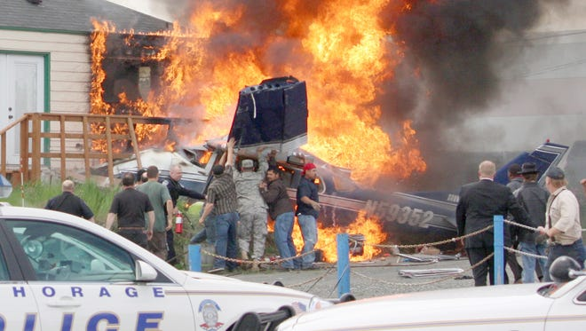 Bystanders and police search the burning wreckage of a Cessna 206 plane for survivors shortly after it crashed in a busy business district near downtown Anchorage during rush-hour Tuesday, June 1, 2010. A small child was killed and four other people on board were injured.