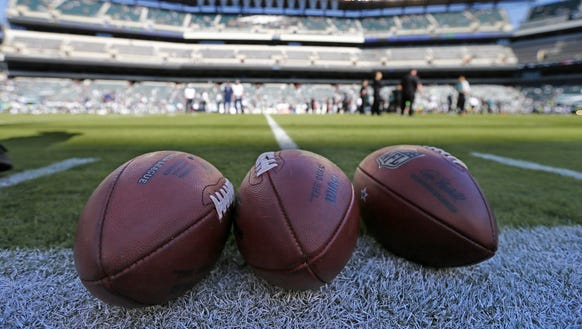 Three footballs sit on the field before a game between