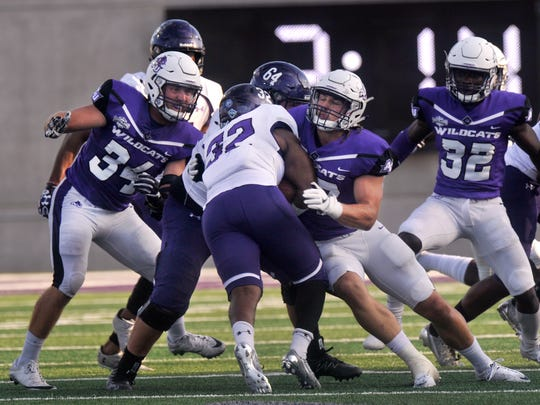 Stephen F. Austin University running back Jamall Shaw runs into Abilene Christian University defensive end Dylan Douglass (right) and linebacker Sam Denmark during Saturday's game at Wildcat Stadium Sept. 23, 2017. ACU lost, 10-20.