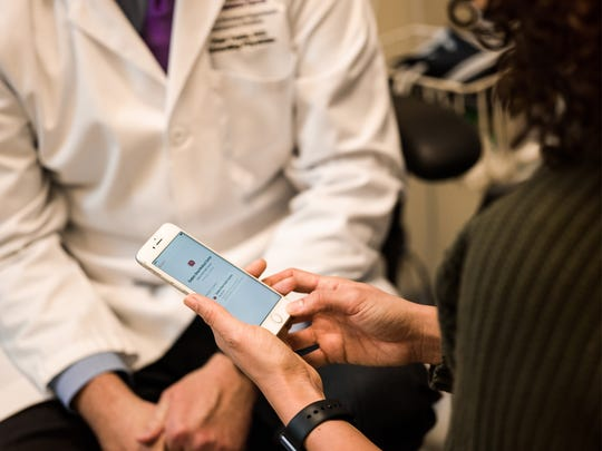 A woman meeting with a doctor looking at health records on her iPhone
