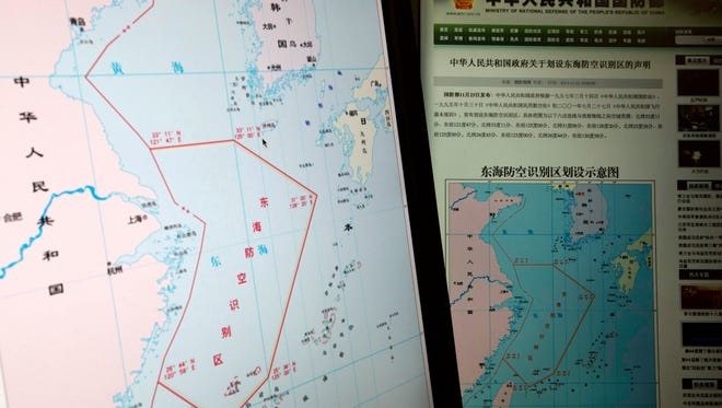 In this Nov. 26, 2013, photo computer screens display a map showing the outline of China's new air defense zone.