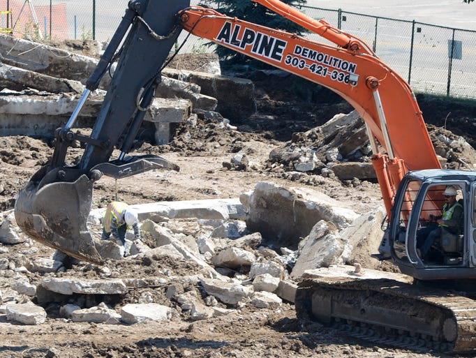 An excavator looks to remove debris as construction continues at the Foothills Mall Thursday Jun 26, 2014.