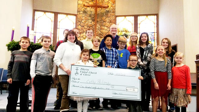 The children of Pilgrim United Church of Christ and Pastor Ted Drewsen present Cathy Philipski of the Department of Community Programs a check to help those with special needs children.