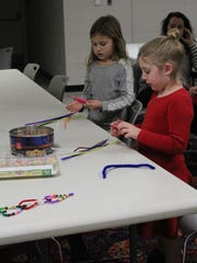 Elle Monaghan (right) and Kendall Husta (left), both 5, begin working on their Valentine's Day craft.